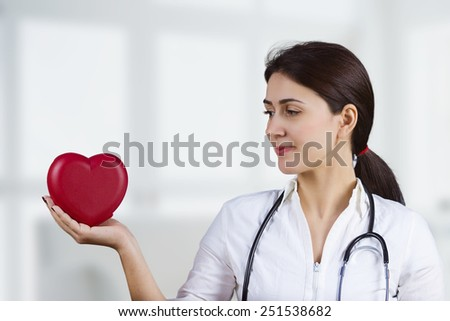 Smiling Female doctor holding and looking to a red heart with stethoscope.Medicine,Health care,Hospital. - stock photo