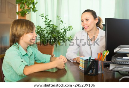 Smiling female doctor talking with a teenager in her office - stock photo