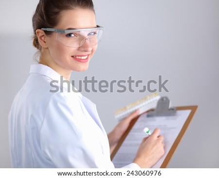 Smiling female doctor with a folder in uniform standing - stock photo