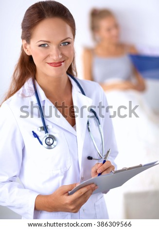 Smiling female doctor with a folder in uniform standing at hospital