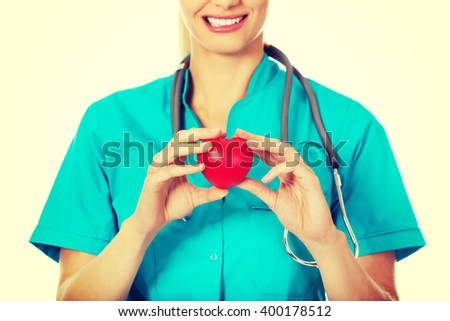 Smiling female doctor with stethoscope holding heart model - stock photo