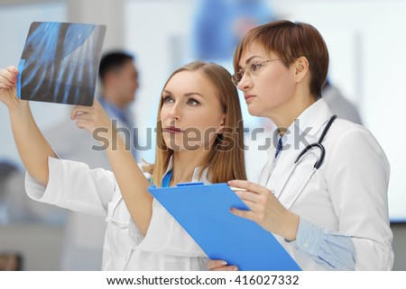 Smiling female doctors examining x-ray in the hospital, close-up