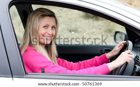 Smiling female driver at the wheel in her new car - stock photo