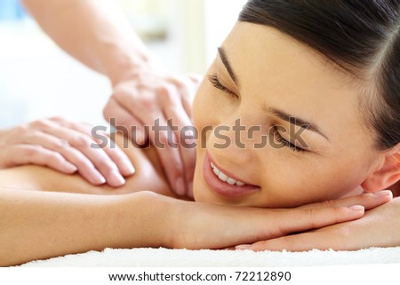 Smiling female during luxurious procedure of massage - stock photo