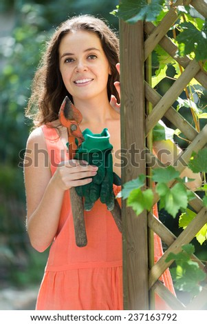 Smiling female florist working with pruning scissors in the garden  - stock photo
