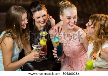 Smiling female friends interacting with each other while having cocktail at bar