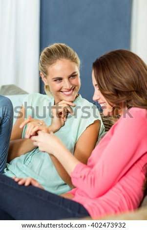 Smiling female friends sitting in living room at home