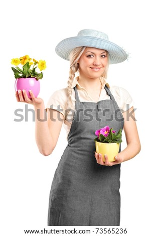 Smiling female gardener holding two potted plants isolated on white background - stock photo