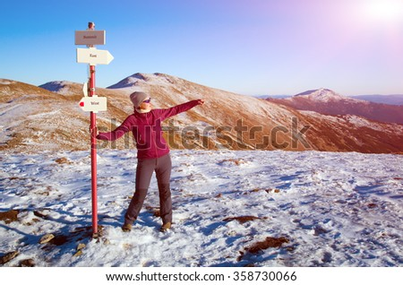 Smiling Female Hiker staying at Path Sign and admiring scenic View in Winter Mountains pointing with her Hand to Horizon   - stock photo