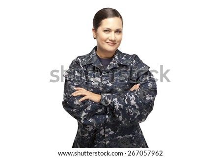 Smiling female in navy uniform with arms crossed posing against white background - stock photo
