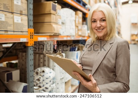 Smiling female manager holding clipboard in a large warehouse - stock photo