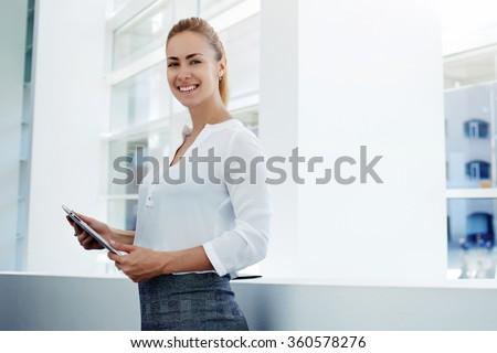 Smiling female managing director holding digital tablet while standing in modern office interior during work break, cheerful businesswoman holding touch pad while preparing for the important meeting - stock photo