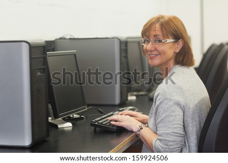 Smiling female mature student using a computer looking at camera - stock photo