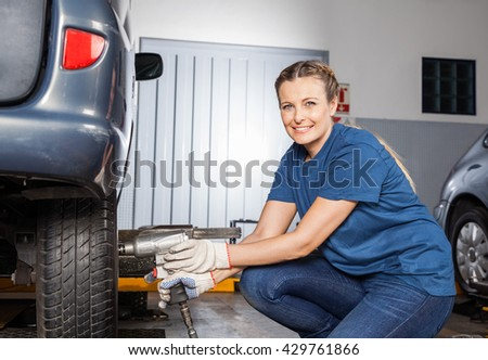 Smiling Female Mechanic Fixing Tire With Pneumatic Wrench - stock photo