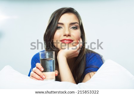 Smiling female model portrait with water glass. Beautiful girl. Young woman drink water. - stock photo