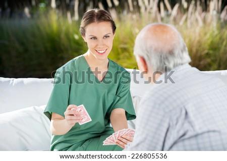 Smiling female nurse playing cards with senior man at nursing home - stock photo