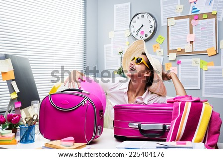 Smiling female office worker ready to leave for vacations with pink luggage. - stock photo