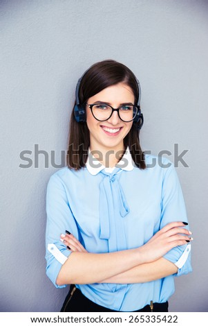 Smiling female operator with phone headset and arsm folded over gray background. Wearing in blue shirt and glasses. Looking at camera - stock photo