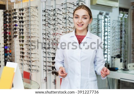 Smiling female optician offering professional help in ophthalmologic shop