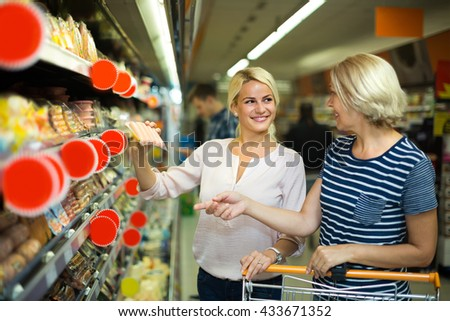 Smiling female pensioner and her adult  daughter choosing chilled sausages in shop