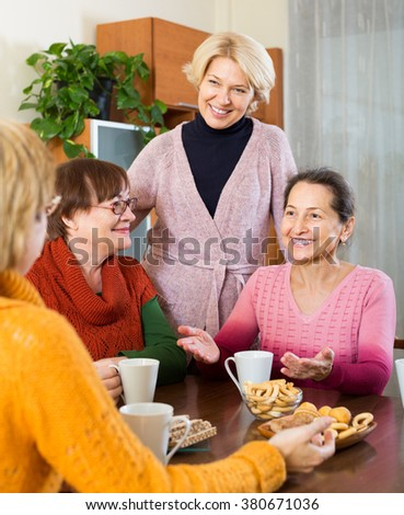 Smiling female pensioners drinking coffee and talking