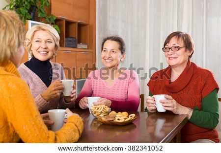 Smiling female pensioners drinking coffee at home and talking - stock photo