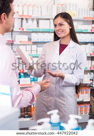 Smiling female pharmacist in drugstore consulting customer about medication