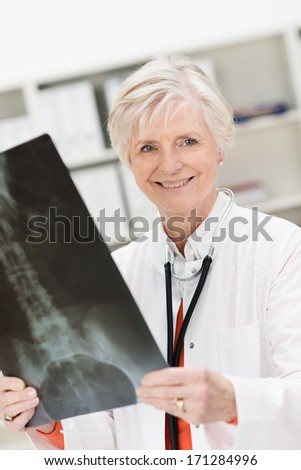 Smiling female physician or radiologist checking a pelvic x-ray in the hospital following orthopaedic surgery or to make a diagnosis - stock photo