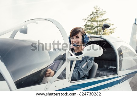 Smiling female pilot in the light aircraft cockpit, she is wearing aviator headset and checking controls