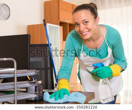 Smiling female professional cleaner making cleaning in the office-room