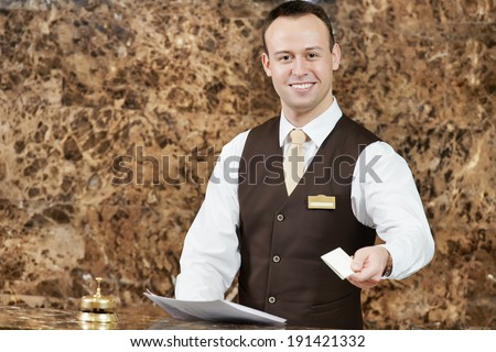 smiling female receptionist passing key card to guest - stock photo