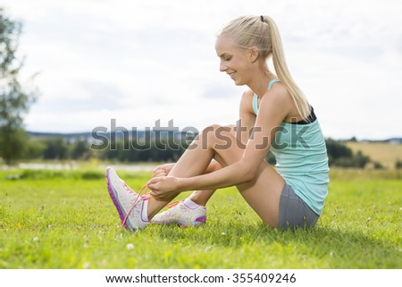 Smiling female runner tying shoe laces at the grass - stock photo