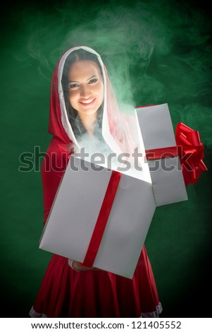 Smiling female Santa opening the magic Christmas present box on dark green background