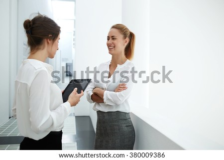 Smiling female secretary talking with boos while standing in modern office interior during work break, woman holding touch pad while speak with her business partner during met in hallway company - stock photo