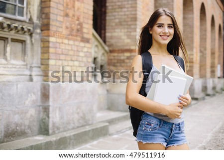 smiling female student in black eyeglasses with folders