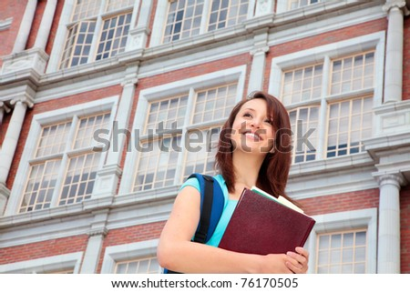 Smiling female student in front of school
