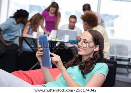 Smiling female student using digital tablet with friends in background - stock photo