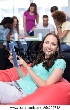 Smiling female student using digital tablet with friends in background