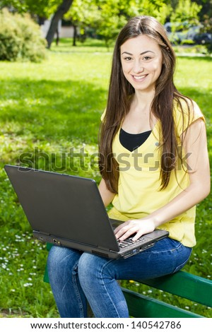 Smiling female student using laptop in the park. - stock photo