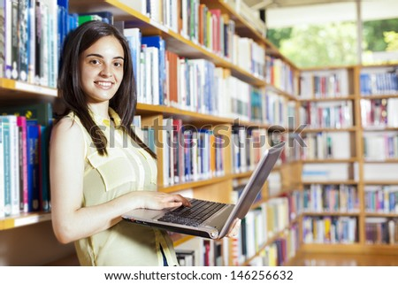 Smiling female student with laptop in a high school library - stock photo