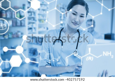 Smiling female surgeon using a laptop against pharmacist with grey hair standing behind shelves of drugs - stock photo