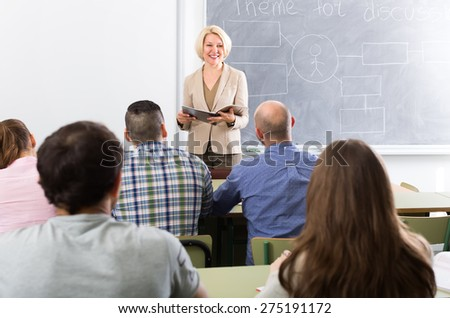 Smiling female teacher lecturing adult students in a university - stock photo