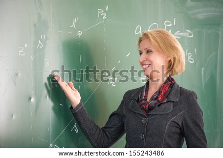 Smiling female teacher pointing to a blackboard - stock photo