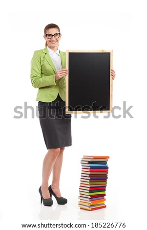 Smiling female teacher standing close to colorful stack of books and holding a blackboard. Full length studio shot isolated on white. - stock photo