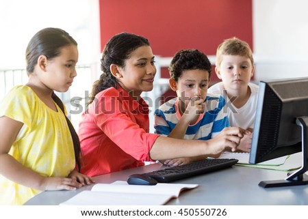 Smiling female teacher teaching computer to children in classroom