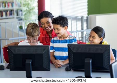 Smiling female teacher with children during computer class - stock photo