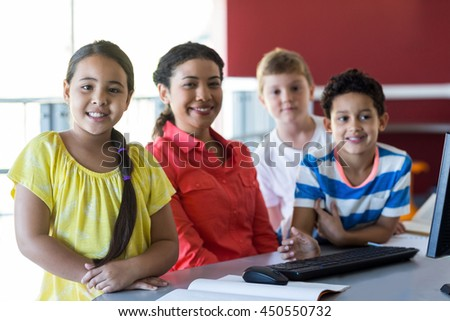 Smiling female teacher with children in computer room - stock photo