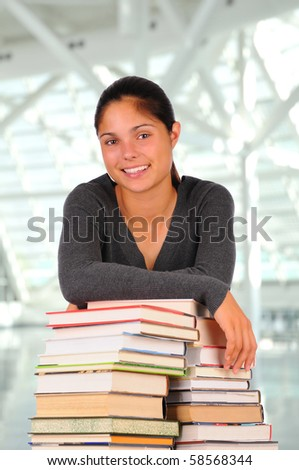 Smiling female teenage student leaning on a stack of books. Horizontal format in modern library building. Back to school concept. - stock photo