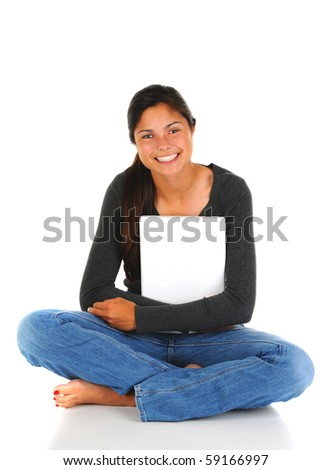 Smiling female teenage student sitting with her legs crossed clutching her closed laptop computer. Vertical format isolated on white. - stock photo