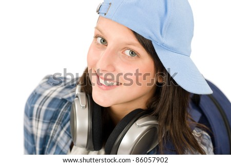 Smiling female teenager enjoy music with headphones and baseball cap